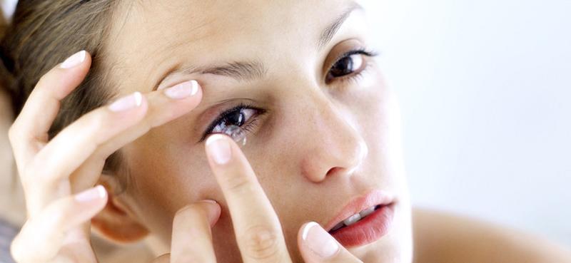 Nainen asettaa piilolinssit silmiinsä